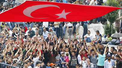 Толпа мигрантов из Сирии у главного автовокзала под турецким флагом в Стамбуле, Турция