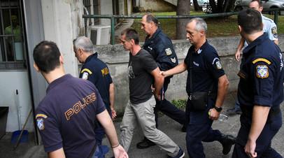Александр Винник в сопровождении сотрудников полиции