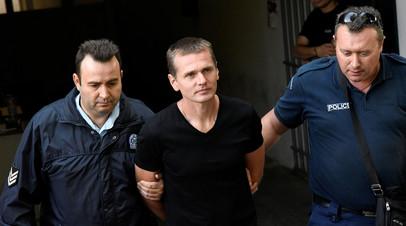 Александр Винник, сопровождаемый сотрудниками полиции, покидает суд в Салониках