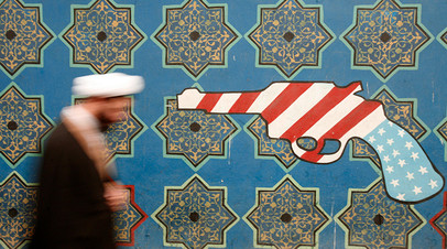An Iranian cleric walks past a mural on the wall of the former U.S. embassy in Tehran