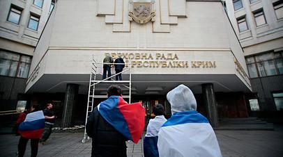 Крымчане снимают вывеску Верховной Рады Украины со здания парламента на полуострове. 18 марта 2014 года.