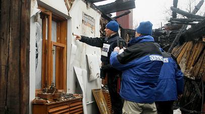 Сотрудники миссии ОБСЕ проводят осмотр разрушенного при обстреле жилого дома в Донецке
