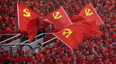 Студенты с флагами Коммунистической партии Китая на Олимпийском стадионе в г. Чунчин, КНР