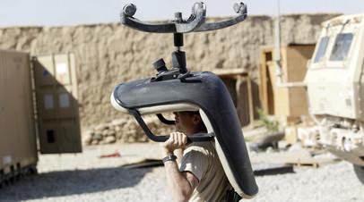 Солдат армии США несёт кресло в  фургон, Южный Афганистан