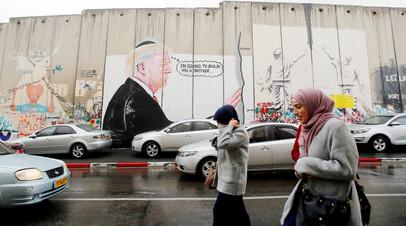 Палестинцы в Вифлееме проходят мимо граффити, изображающих президента США Дональда Трампа