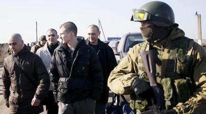 Военнослужащие ДНР охраняют украинских военнопленных во время процедуры обмена в районе населённого пункта Александровка
