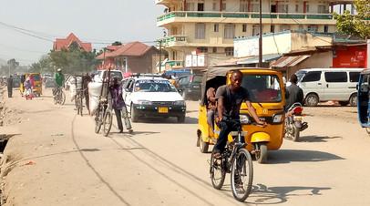 Велосипедисты и автомобилисты ездят по главной улице Увиры в провинции Южное Киву Демократической Республики Конго