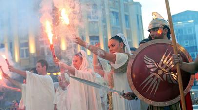 Участники костюмированного шествия в центре Скопье на фоне статуи Александра Македонского