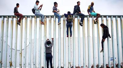 Мигранты на пограничном заборе между Мексикой и США