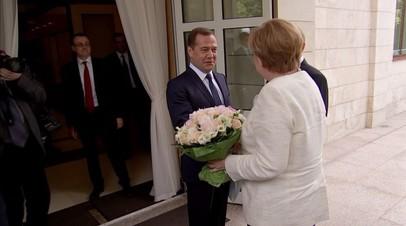 Меркель на русском языке пожелала Медведеву счастливого пути