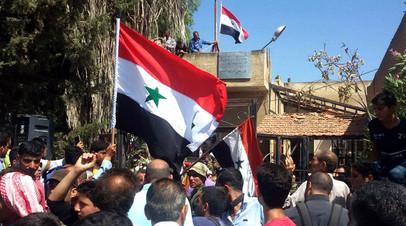 Сирийцы держат флаг своей страны на площади города Тафас в провинции Дараа после того, как населённый пункт перешёл под контроль правительственных сил
