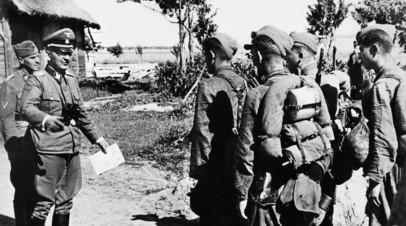 Командир бригады ваффен СС (второй слева) и командир дивизии беседуют с галицкими добровольцами.