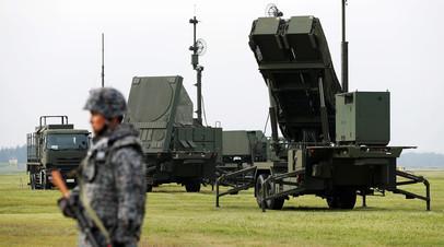Военнослужащий армии Японии около  американского противоракетного комплекса «Патриот» на авиабазе ВВС США  в Токио