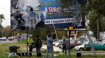 Активисты оппозиции срывают плакат, размещённый в рамках кампании властей против деятельности Сороса в стране. Венгрия, Будапешт