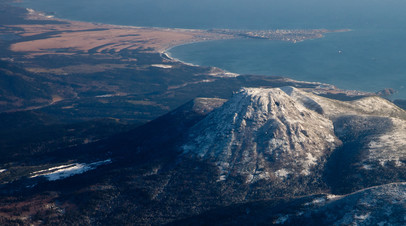 Вид на вулкан Менделеева и посёлок Южно-Курильск на острове Кунашир