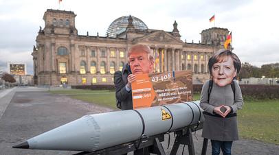 Антивоенные активисты в масках Дональда Трампа и Ангелы Меркель перед бундестагом