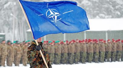 Немецкий военнослужащий с флагом НАТО в руках на военной базе в Рукле