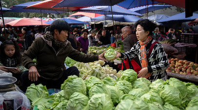 A customer (R) buys vegetables at a market in Beijing on October 16, 2018