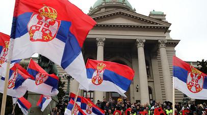 Демонстранты с сербскими флагами во время протеста против президента Сербии Александра Вучича возле здания парламента в Белграде. Сербия, 13 апреля 2019 года