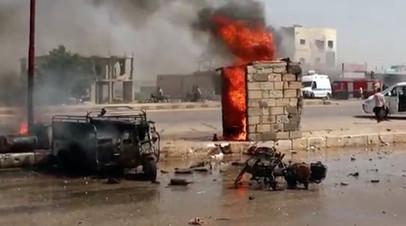 Сгоревший автомобиль и мотоцикл на дороге в Саракибе, Сирия