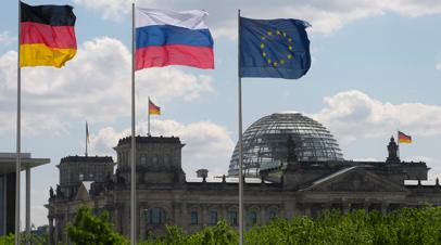 Флаги Германии, России и ЕС (слева направо) на фоне Рейхстага