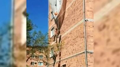В Приморье десантник зацепился парашютом за крышу дома и повис на высоте третьего этажа — видео