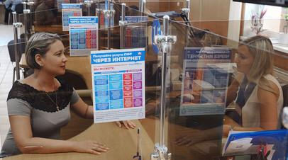 Специалист клиентской службы управления Пенсионного фонда России обслуживает клиента в городе Тамбове