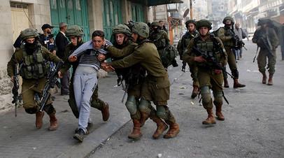 Израильские солдаты задерживают палестинца на территории Западного берега реки Иордан