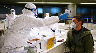 Медицинский работник измеряет температуру у пассажира в аэропорту Внуково