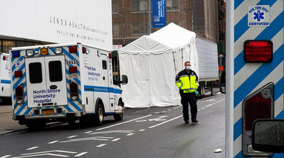 A paramedic walks next to a makeshift morgue set outside Lenox Health Medical Pavilion as the coronavirus disease (COVID-19) outbreak continues in New York, U.S., March 29, 2020