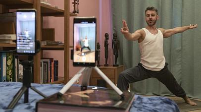 Инструктор проводит трансляцию и видеозапись урока йоги у себя дома в Санкт-Петербурге