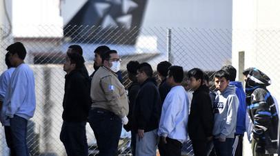 Сотрудник иммиграционной службы в защитной маске рядом с мигрантами, депортированными из Соединённых Штатов, Гватемала, март 2020 года