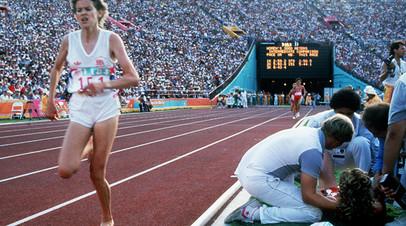 Зола Бадд преодолевает очередной круг финала бега на 3000 метров на Олимпиаде в Лос-Анджелесе, пока врачи и тренеры оказывают помощь Мэри Деккер