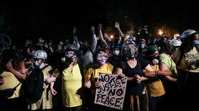 Группа матерей стоит между протестующими и федеральными силовиками во время акции протеста в Портленде