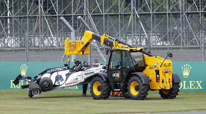 The car of AlphaTauri's Daniil Kvyat is lifted away after he crashed out of the race