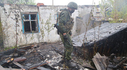 Военнослужащий Народной милиции ДНР осматривает сгоревший дом в поселке Шахты 6-7 в Горловке