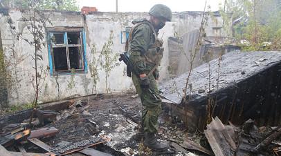 Военнослужащий Народной милиции ДНР осматривает сгоревший дом в посёлке Шахты