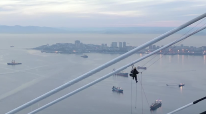 Альпинист очищает от наледи мост на остров Русский — видео с беспилотника