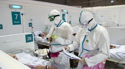 Медицинские работники во время осмотра пациента во временном госпитале для больных COVID-19, развёрнутом в ледовом дворце «Крылатское»