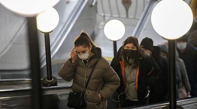 Пассажиры в защитных масках на эскалаторе в московском метрополитене