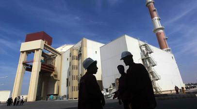 Иранские рабочие стоят перед Бушерской АЭС